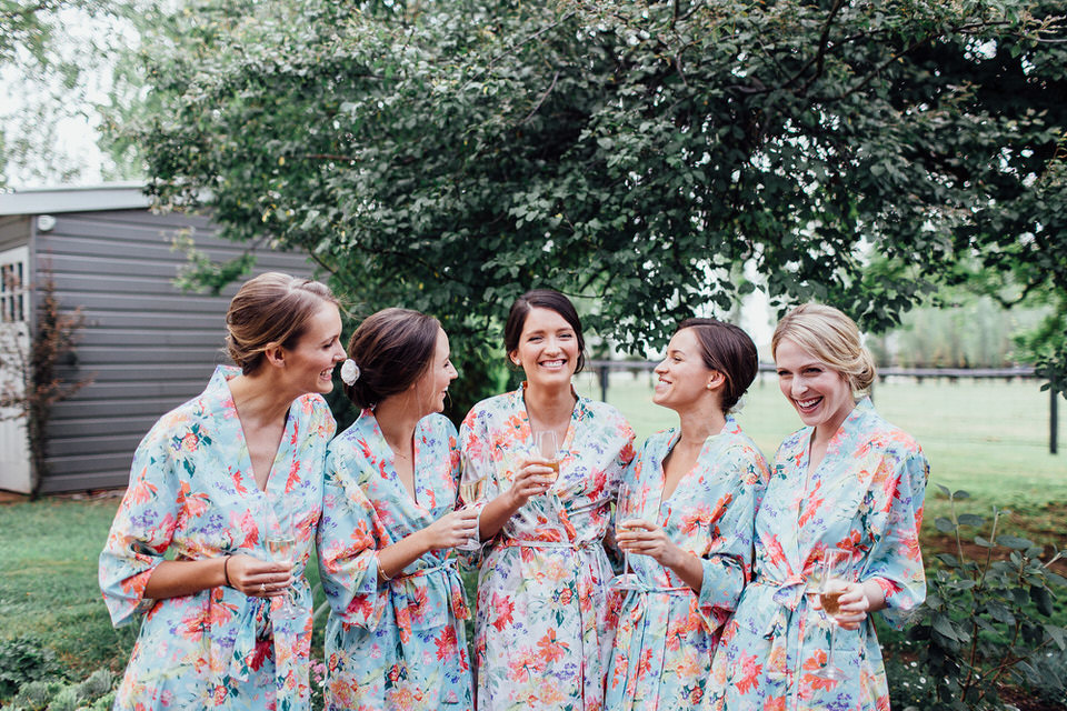 bridesmaids and bride in floral robes getting ready for wedding at bendooley estate homestead in bowral southern highlands