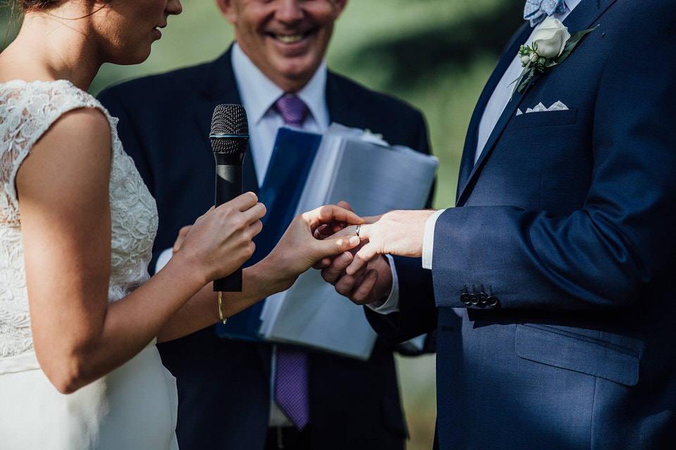 bride and groom exchanging rings at wedding ceremony at bendooley estate in bowral southern highlands