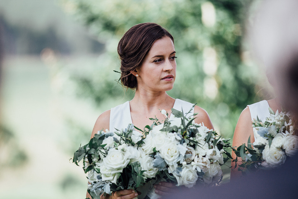 bridesmaid holding flowers at wedding ceremony at bendooley estate in bowral southern highlands