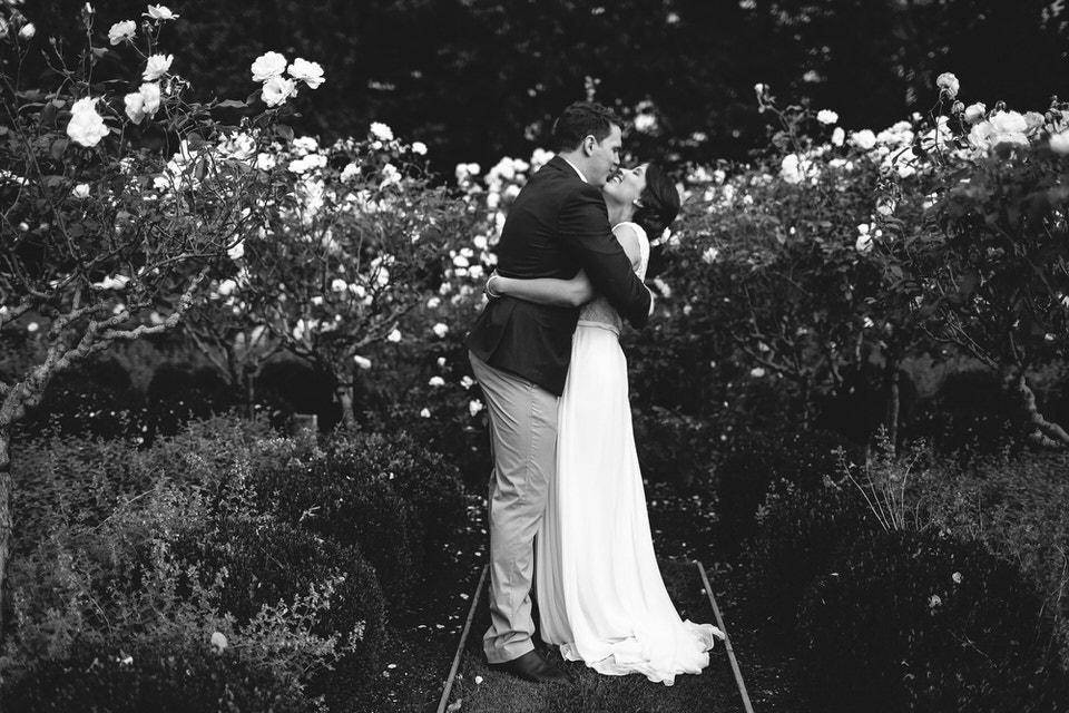 bride and groom at bendooley estate rose garden in bowral southern highlands