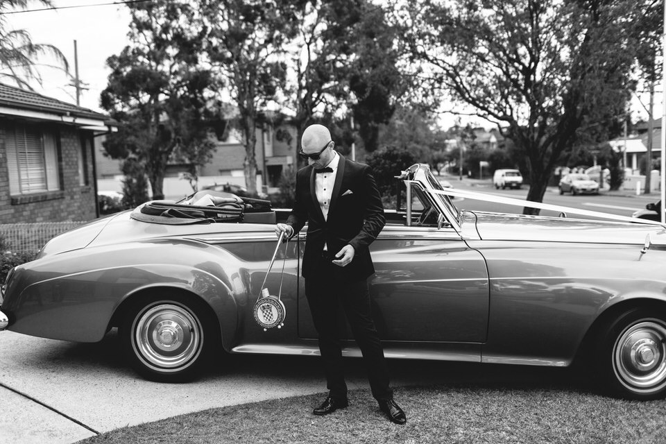 Groom standing in front of vintage car before wedding ceremony