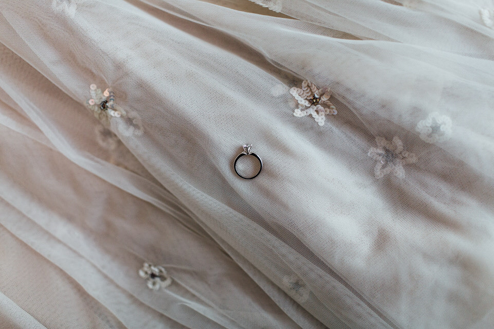 Engagement ring placed on Needle and Thread London wedding dress