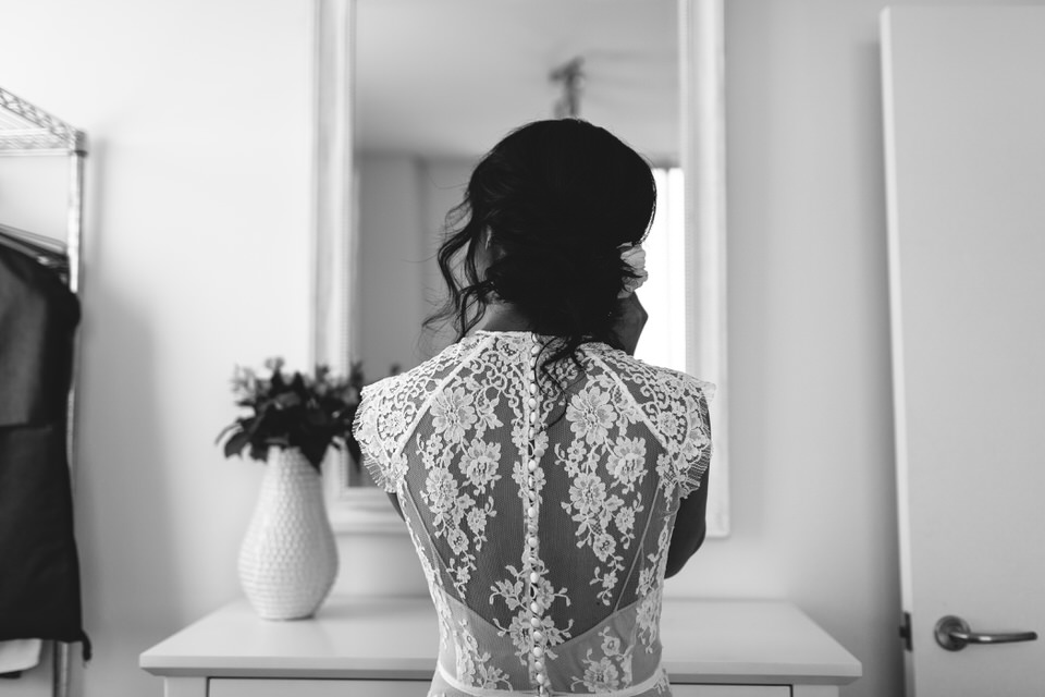 Back of bride putting on earrings and bride wearing Rue De Seine lace wedding dress