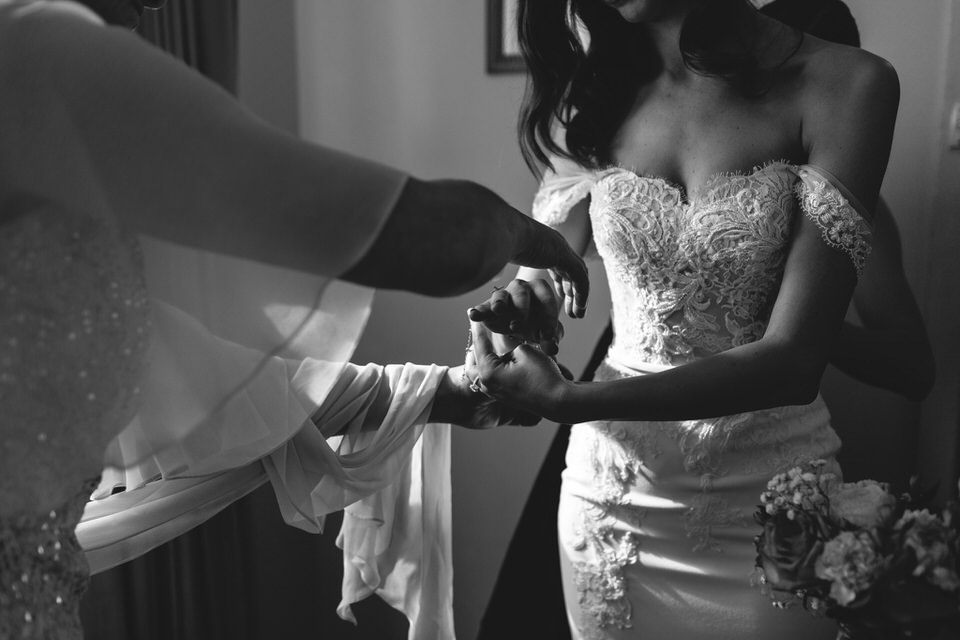 Mother of the bride placing a bracelet on bride's hand