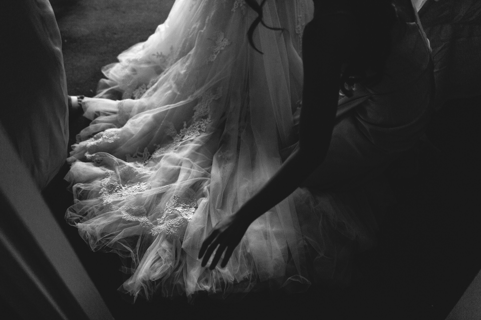Bridesmaid fixing brides dress before ceremony