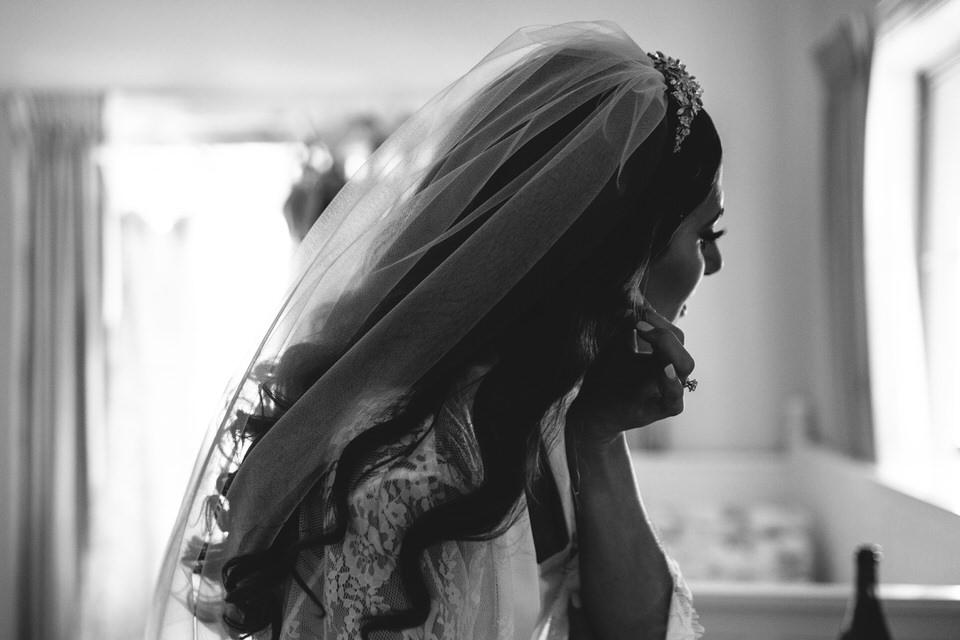 Bride wearing veil and putting on earrings at Terara Riverside Retreat