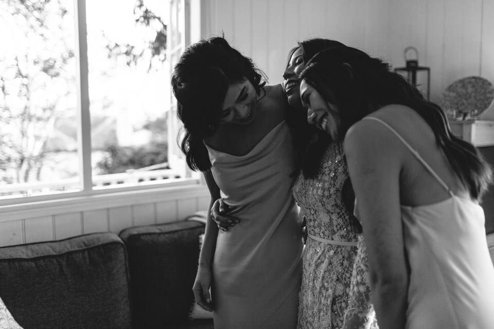Bride and bridesmaids hugging before wedding ceremony in Southern Highlands