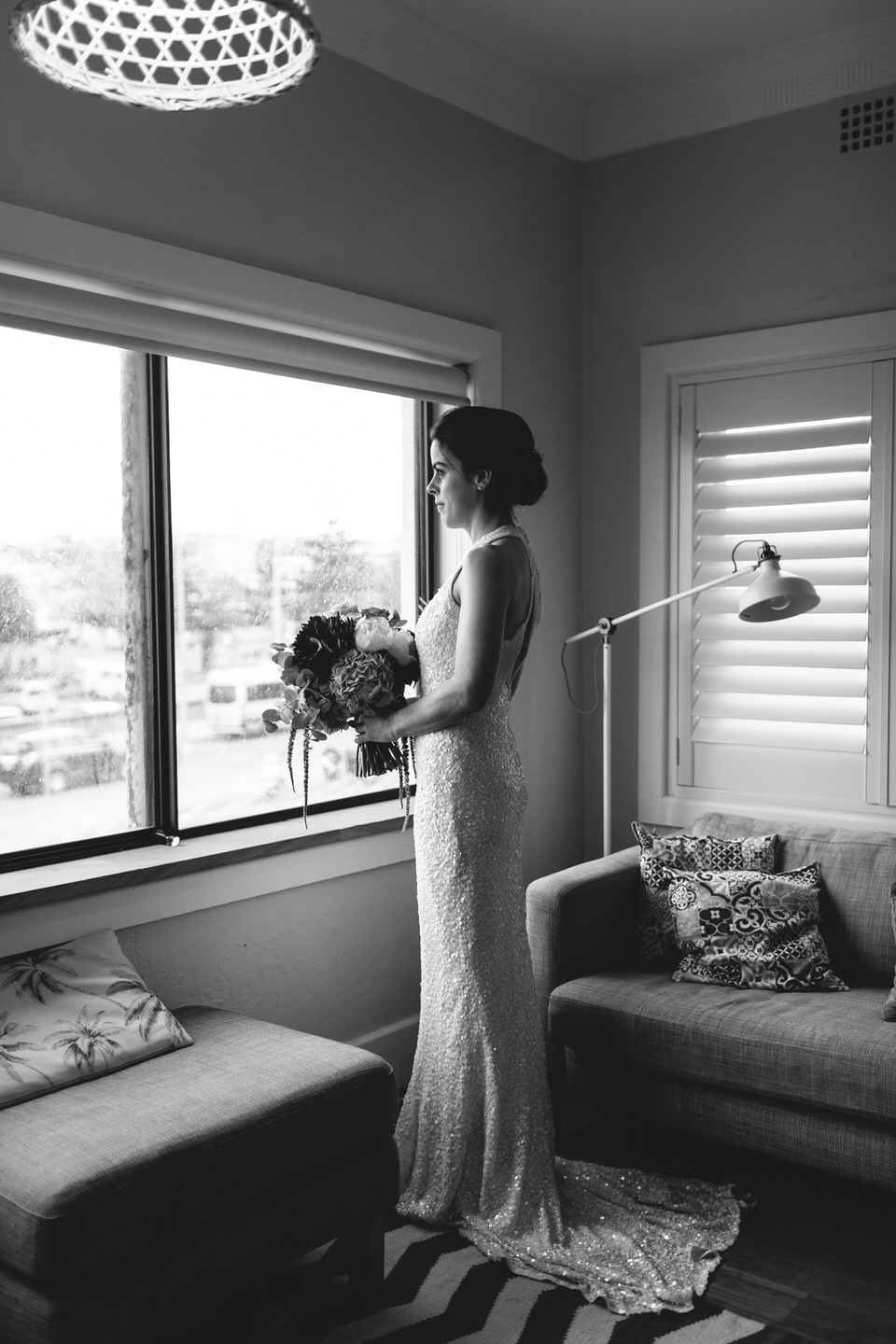 Bride standing by window wearing sequinned dress by Karen Willis Holmes and holding bouquet made by Maggie May flowers