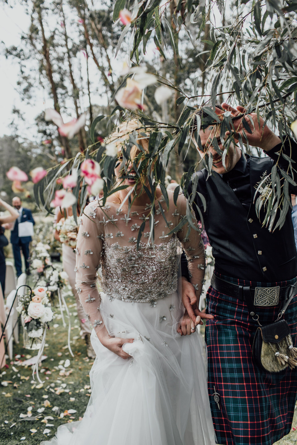 Bride and groom walking down aisle at Wombat Hollow after wedding ceremony to cheers and confetti