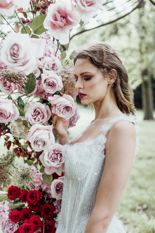 Garden bride standing next to floral arch