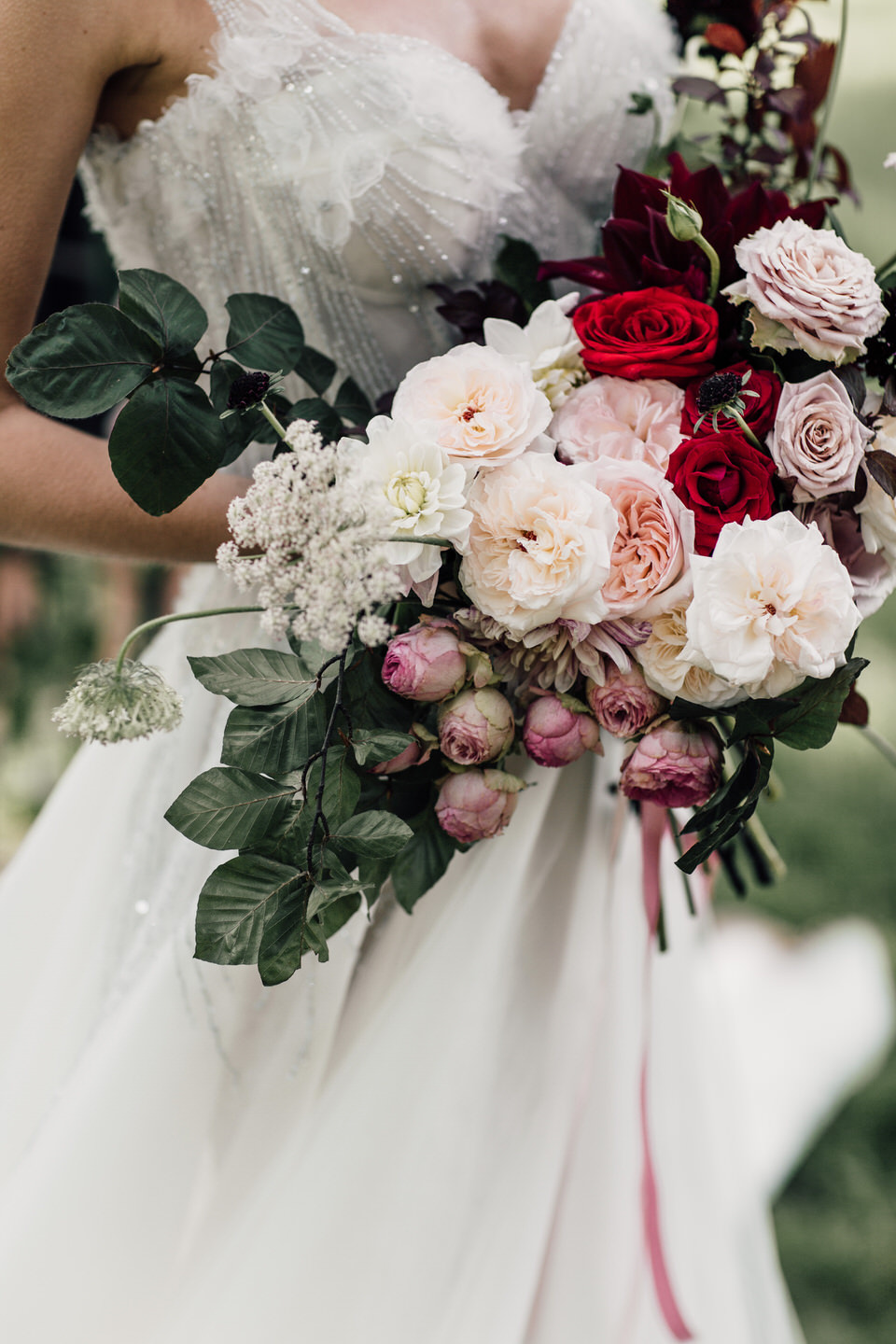 Bride holding romantic wedding bouquet made of David Austin roses and garden roses