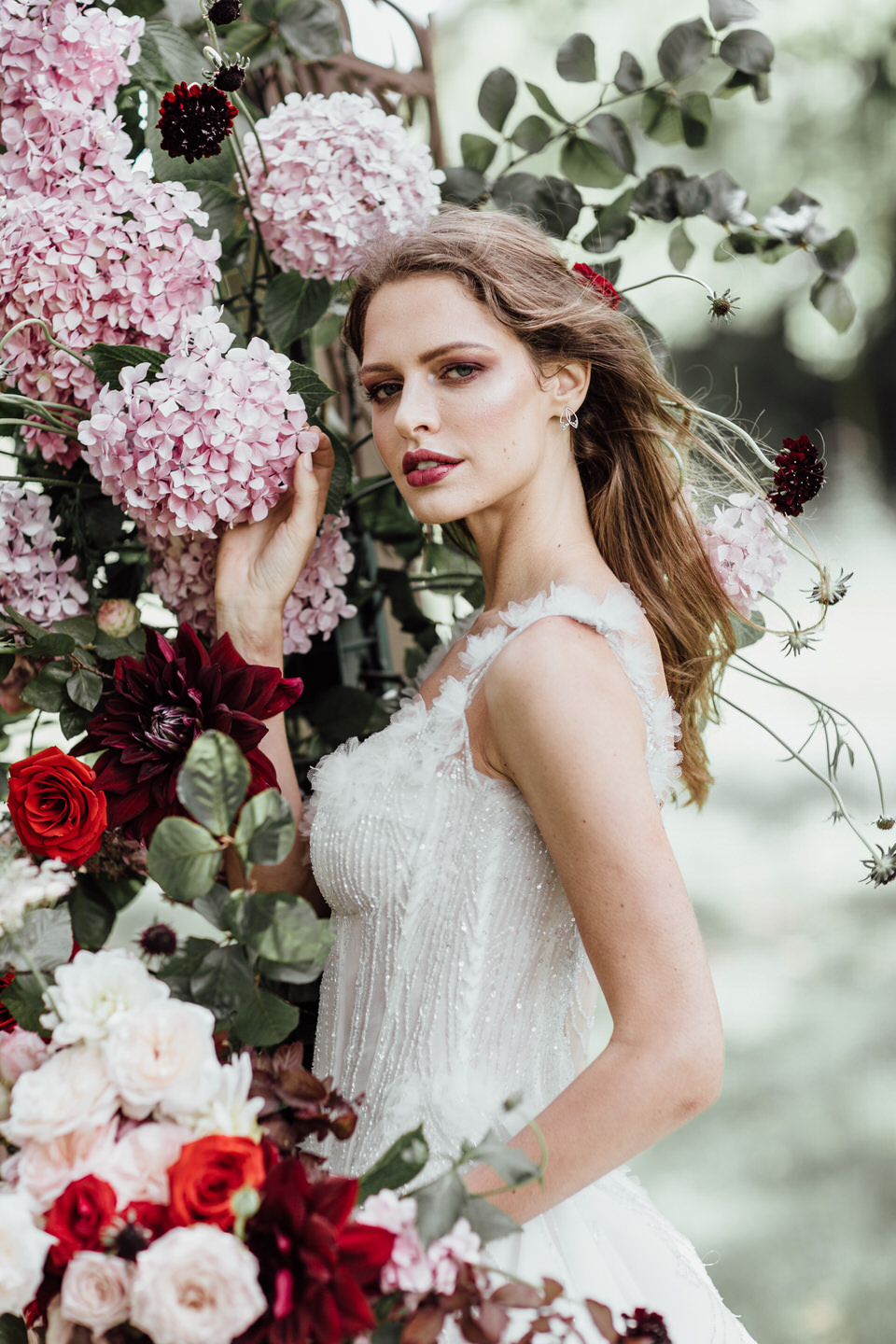 Garden bride standing next to floral arch made up of roses and hydrangeas