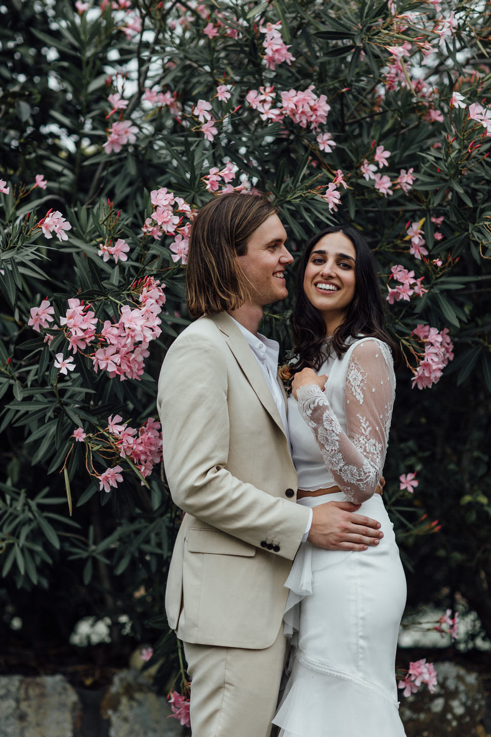 Bride and groom in front of oleander tree in relaxed Sydney backyard wedding
