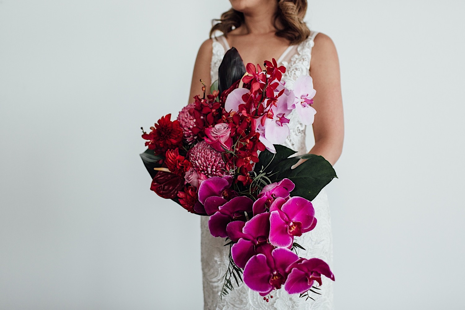 Sydney bride holding colourful bouquet of pink orchids and roses
